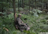 Czyżby zasadzka? Żołnierz pada na ziemię i ogląda skąd padł strzał, który ranił jego kolegę.