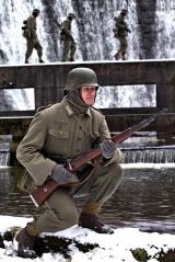 Żołnierz obserwuje teren podczas gdy jego koledzy pokonują rzekę.