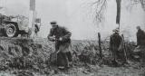 Żołnierze Kampfgruppe Hansen przemieszczają się wzdłuż drogi, na płaszczu pierwszego widoczny orzełek SS na ramieniu.